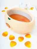 Orange paraffin wax in bowl. Manicure in beauty spa salon. poster