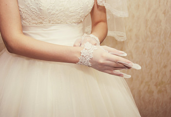 beautiful bride puts on a white glove