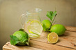 Lemons with leaves and water jug on wooden table
