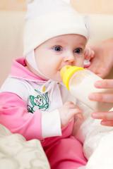 Baby is drinking milk from bottle