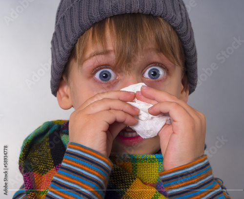Beautiful boy wipes nose with napkin