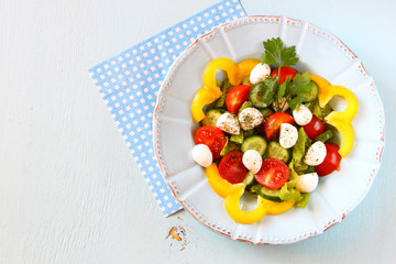 salad with mozzarella and fresh vegetables on wooden table backg