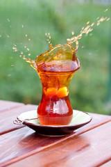 a glass of black tea, splash