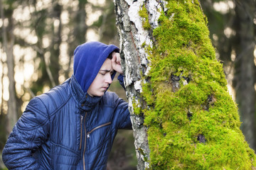 Sorrowful boy  leaning on a tree