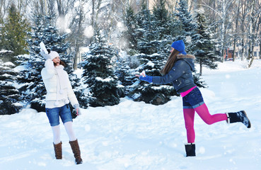 Two girls in winter throw oneself snow