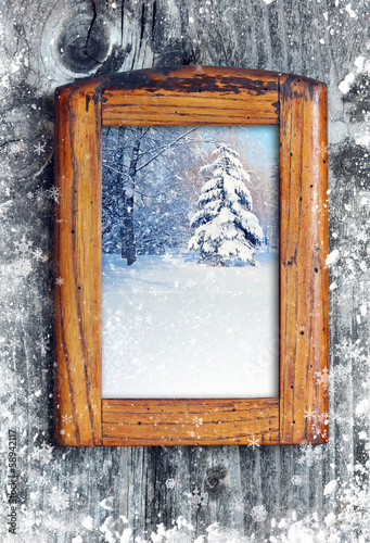 Frame with winter landscape on a snow-covered wooden background