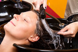 Hairdressers hand washing female customer's hair in salon