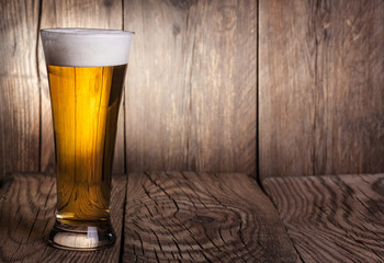 Mug of beer on wooden background