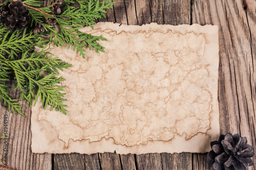 sheet of paper with christmas tree branches and bumps on wooden