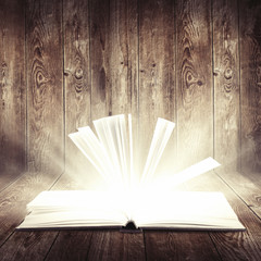 open book with light insideout on wooden background
