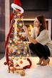 Pretty woman decorating modern christmas tree