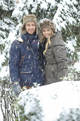 Happy couple embracing in winter forest
