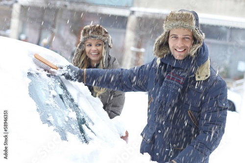 Happy couple brushing off snow from car