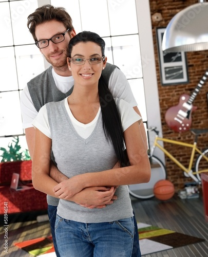 Trendy young couple cuddling at home