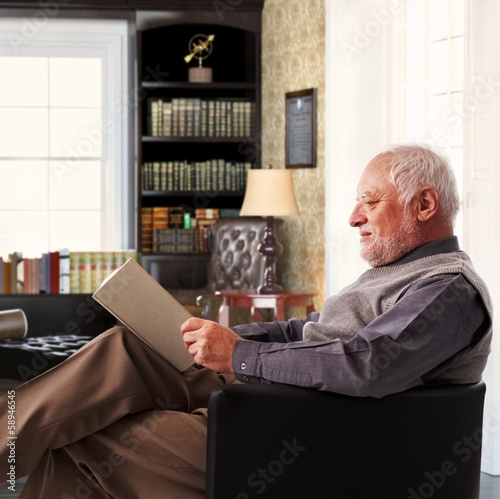 Elderly man reading book at study at home