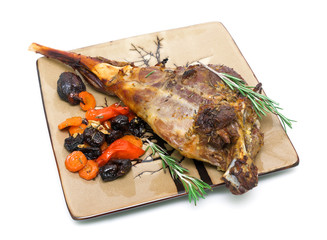 baked leg of lamb with carrots, prunes and rosemary on a plate o
