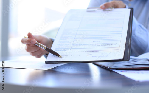 Businesswoman holding pen pointing at signature