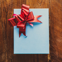blue gift box with red ribbon on wood for vintage
