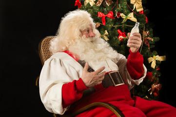 Happy Santa Claus drinking milk from glass bottle