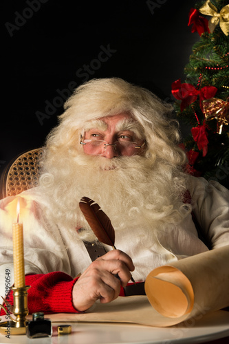 Santa Claus sitting at home and writing a letter