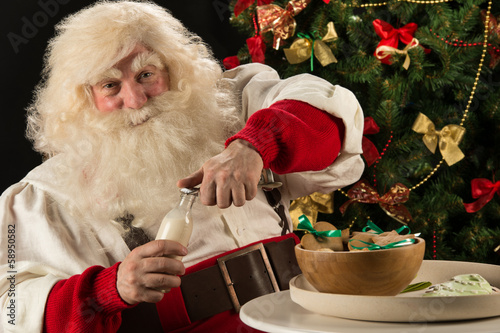 Santa Claus eating cookies with milk