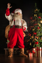 Real Santa Claus carrying big bag full of gifts, at home near Ch