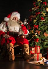 Santa Claus calling by vintage phone. Sitting near Christmas tre