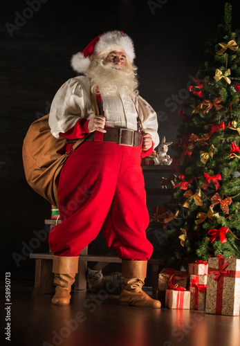 Real Santa Claus carrying big bag full of gifts, at home near Ch