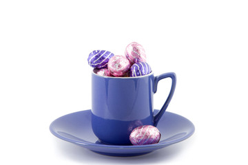 purple cup and saucer filled with chocolate Easter eggs