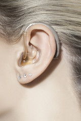 Beautiful woman ear with hearing aid