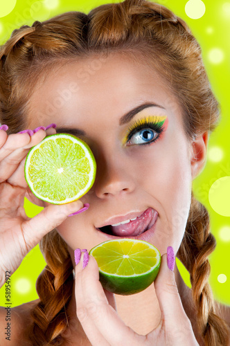 Beautiful woman holds lime in her hands