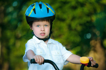 Close up portrait of a cute little boy on bicycle