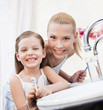 Little smiling girl brushes her teeth with her mom