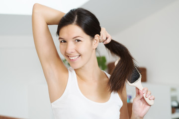 Smiling woman brushing her hair