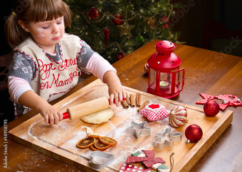 Little girl baking Christmas cookies cutting pastry with a cooki