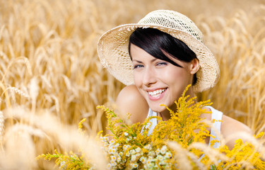 Pretty girl in straw hat and white T-shirt against rye field