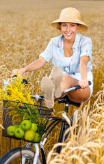 Girl rides bicycle putting legs on it in rye field
