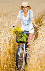 Girl rides cycle with apples and flowers in rye field