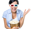 Viewer watching 3D cinema in glasses with bowl full of popcorn