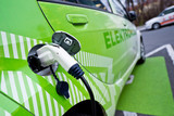 Detail of ecological green car re-fuelling, plugged in poster