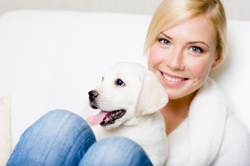 Close up of woman in white sweater with white puppy