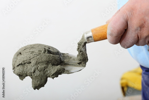 Hand holding a bucket trowel with cement mortar
