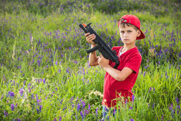 Boy holding a gun in the field.