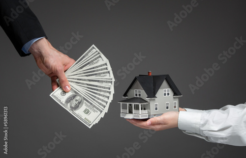 Close up of hands giving house model to other hands with money - 58961313