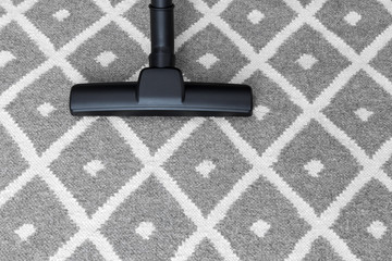 Vacuum cleaner on gray carpet