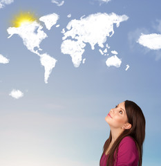Young girl looking at world clouds and sun on blue sky