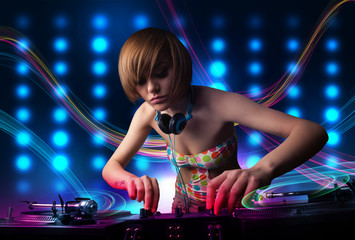 Young Dj girl mixing records with colorful lights