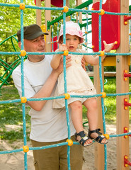 child and father on  playground