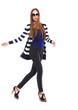 Pretty young woman in stripy shirt walking in studio