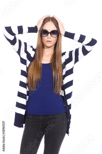 Pretty young woman in stripy shirt walking in studio